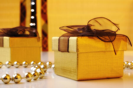 two gift boxes with golden pearls and yellow background