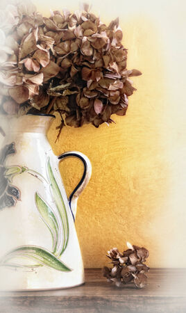 detail of white vase with dried hydrangeas on a table