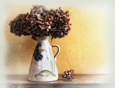 white vase with dried hydrangeas on a table photo