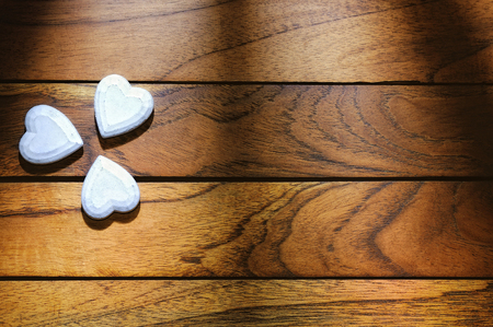 hearts forming a clover with shadows on the wood