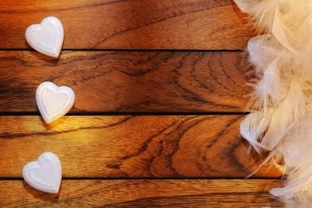 three white hearts misaligned with wood and feathers