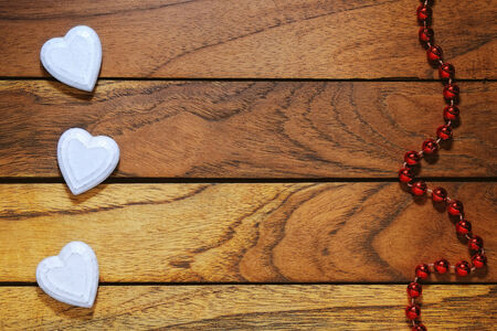 three white hearts misaligned with wood with necklace Stock Photo