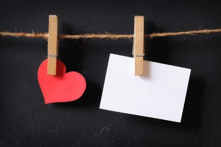 heart with empty poster hanging with blackboard background