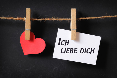 heart with ich liebe dich poster hanging with blackboard background Stock Photo