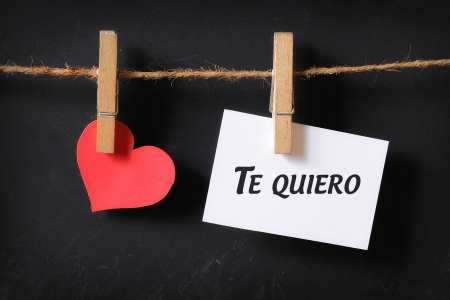 heart with te quiero poster hanging with blackboard background