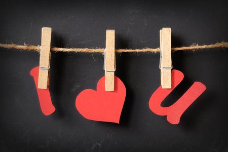 i love u: i love u hanging with blackboard background Stock Photo