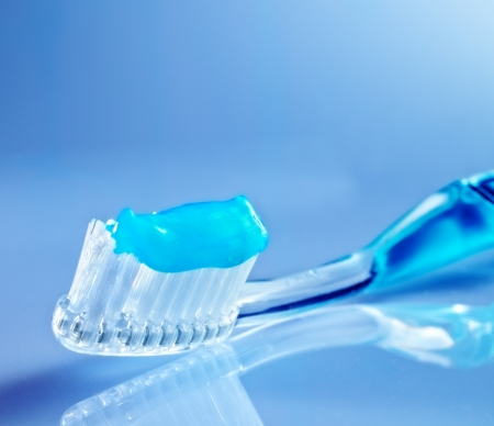 toothbrush on the table with toothpaste and blue background