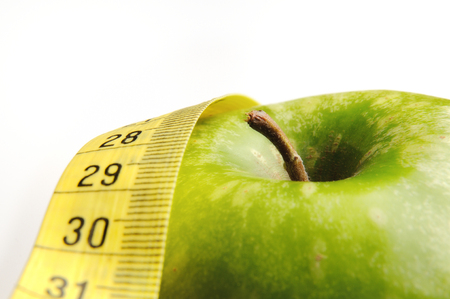 apple and measuring tape isolated for a healthy lifestyle