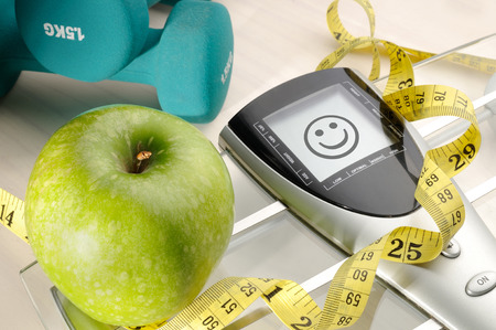 apple, scale and dumbbells for a healthy life and happy face message