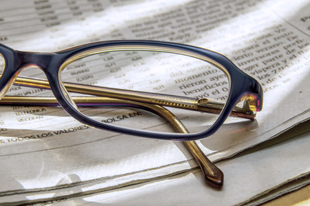 newspaper full of interesting news and reading glasses photo