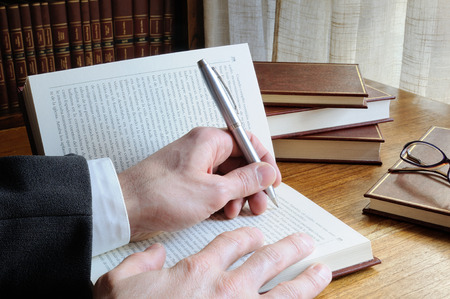 man with pen in hand looking for references in a book Stock Photo