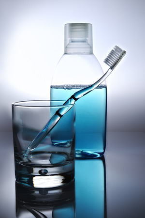 toothbrush, mouthwash and glass, backlit photo