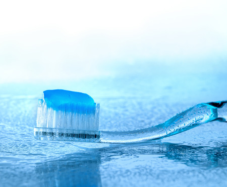 toothbrush with paste on glass with water splashes, backlight Stock Photo