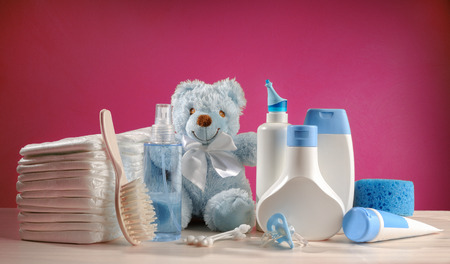 toiletries baby with diapers and pacifiers, and pink background photo