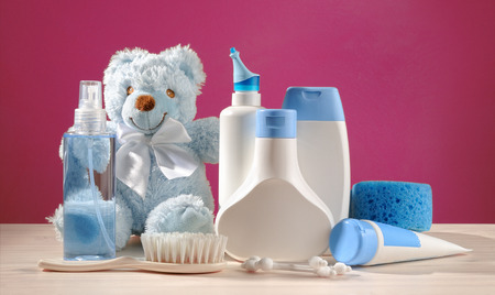toiletries baby, blue items and pink background photo