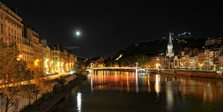 serene view of Saone river at night with church Saint Georges on the right Stock Photo