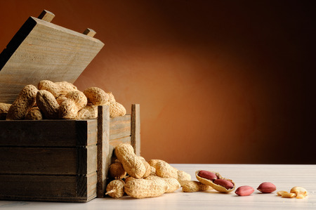 group of peanuts on a white table with trunk wooden container and brown background