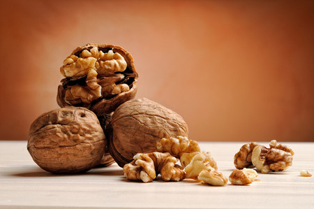 group of walnuts on a white wooden table with brown background Stock Photo