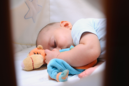 baby sleeping peacefully in his crib