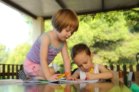 two kids drawing on a notebook in a summer school Stock Photo