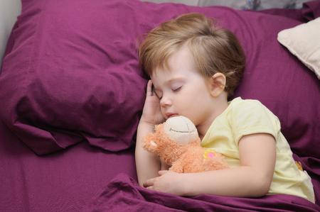 girl sleeping peacefully with her teddy bear between garnets sheets