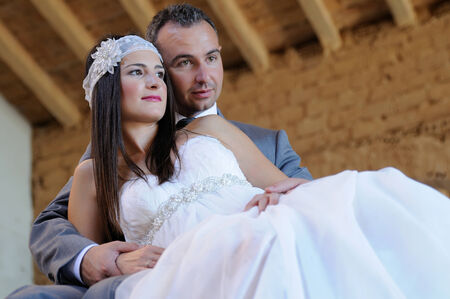 Bride leaning on groom thoughtful in a warehouse in ruins Stock Photo
