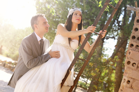groom and bride climbing a rusty ladder on a country house