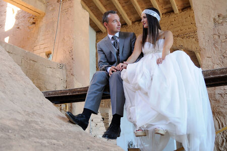 Groom and bride sitting on a scaffolding in a warehouse in ruins