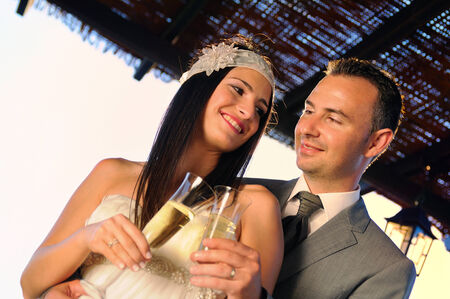 groom and bride toasting with champagne on a terrace smiling eye contact