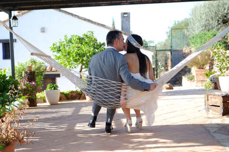groom bride kissing sitting in a hammock rope on the terrace of a country house Stock Photo