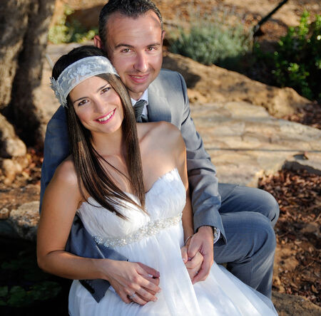 Groom holding the smiling bride sitting on a rock outdoor photo