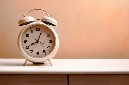 white vintage alarm clock on a wood table Stock Photo