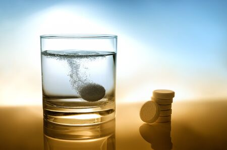 Glass of water with effervescent tablet and pile of pills on the table Foto de archivo