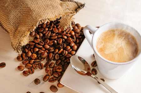 Cup of hot coffee on white wooden table and sack with coffee beans closeup