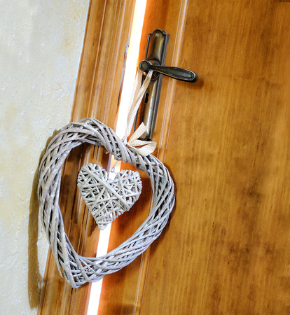 ajar: Two Hearts wicker hanging from the doorknob ajar for a couple in love Stock Photo