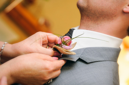 buttonhole: mother putting a flower in the buttonhole suit the groom on their wedding day