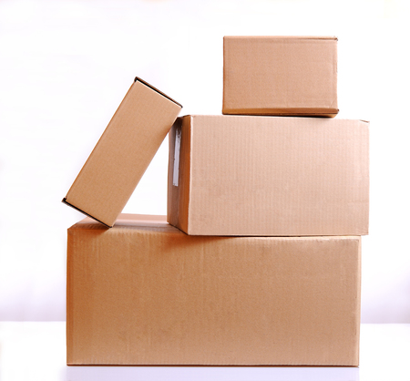 corrugated box: Four brown cardboard boxes isolated over white table Stock Photo