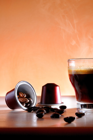 capsules and cup of hot espresso coffee on a table and brown background close up