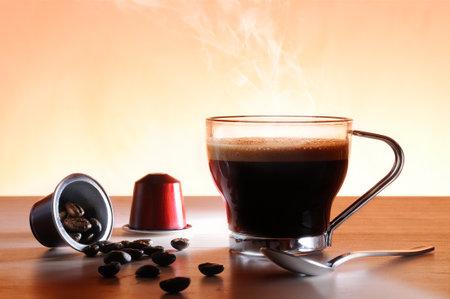 カプセルとテーブルと茶色の背景に熱いエスプレッソ コーヒー カップ
