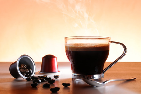capsules and cup of hot espresso coffee on a table and brown background