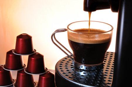 ガラスのコップとカプセルのスタックでエスプレッソ コーヒーを提供するマシン 報道画像