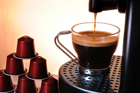 machine serving espresso coffee in a glass cup and stack of capsules