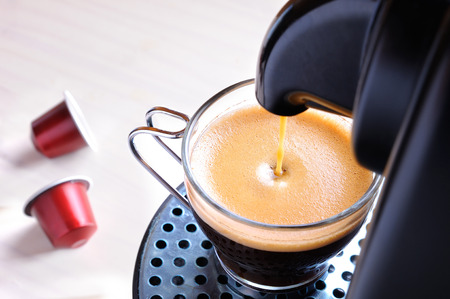 the machine: machine serving espresso coffee in a glass cup and two capsules on the table