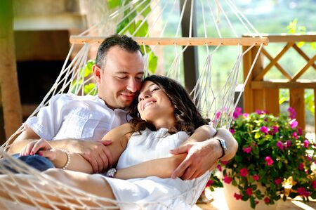 Caucasian young couple dressed in white on a rope hammock on the terrace of a country house lovingly looking