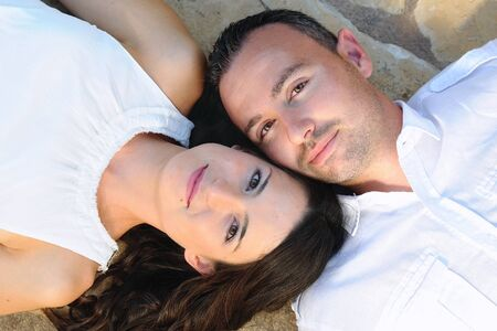 penetrating: Young couple dressed in white lying on a stone floor looking at camera Stock Photo