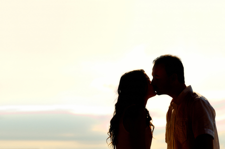 mouth kiss mouth: Silhouette of romantic young couple kissing at sunset backlit