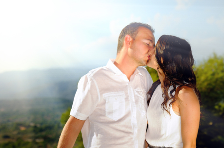 affectionate actions: Young couple dressed in white affectionately kissing in the mountains a sunny day Stock Photo