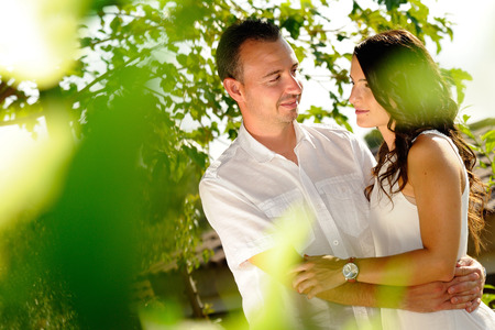 accomplices: Young couple dressed in white looking accomplices among trees in the field Stock Photo