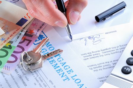 mortgage document: client signing the mortgage loan agreement upon delivery of the keys to a new home rear view Stock Photo