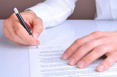 financial agreement: client signing the mortgage loan agreement for the purchase of a new home rear view Stock Photo